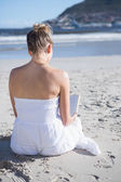 Blonde sitting on beach reading book — Stock Photo
