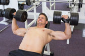Shirtless bodybuilder lifting heavy dumbbells — Stock Photo