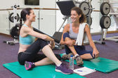 Fit friends chatting on exercise mats — Stock Photo