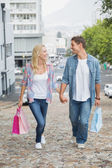 Couple on shopping trip walking uphill — Stok fotoğraf
