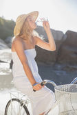 Blonde on bike drinking water at beach — Foto Stock