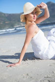 Blonde in white dress sitting on the beach — Stok fotoğraf