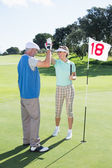 Golfing couple high fiving at eighteenth hole — Stock Photo