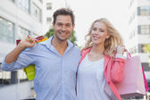 Stylish couple holding shopping bags — Stock Photo