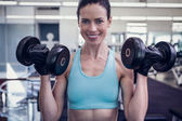 Smiling woman lifting heavy dumbbell — Stock Photo