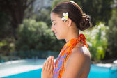 Brunette in sarong meditating by the pool — Stock Photo