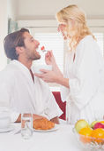 Couple having breakfast in their bathrobes  — Foto de Stock