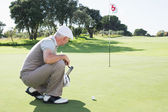 Golfer on putting green at eighteenth hole — Stok fotoğraf