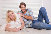 Couple sitting on floor doing crossword — Stock fotografie