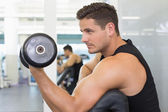 Focused bodybuilder lifting dumbbell — Stock Photo