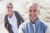 Couple smiling at camera on the beach — Foto de Stock