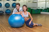 Woman leaning on exercise ball with trainer — Stock Photo