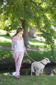 Blonde with her labrador in the park — Stok fotoğraf