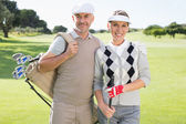 Golfing couple smiling on the putting green — Stok fotoğraf