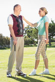 Golfing couple smiling at each other — Stock Photo