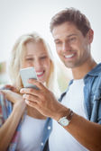 Couple looking at smartphone together — Stockfoto