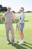 Golfing couple holding clubs — Stock Photo