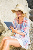 Blonde using tablet pc at beach — Stock Photo