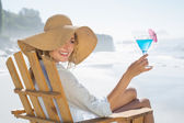 Woman relaxing in deck chair by the sea holding cocktail — ストック写真