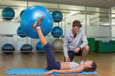 Trainer watching his client lift exercise ball — ストック写真