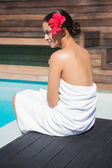 Brunette in towel sitting by the pool — Stock Photo