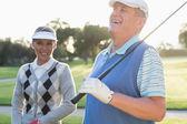 Golfing couple smiling at camera — Stock Photo