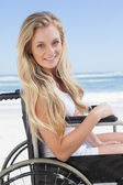 Wheelchair bound blonde smiling on beach — Stock Photo