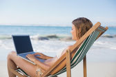 Woman relaxing in deck chair using laptop — Stock Photo