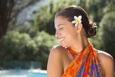 Brunette in sarong smiling by the pool — Stok fotoğraf
