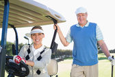 Happy golfing couple on buggy — 图库照片