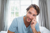 Smiling man sitting on bed — Stock Photo