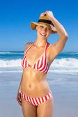 Woman in bikini and sunhat posing on beach — Stock Photo