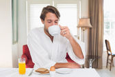 Man in bathrobe drinking coffee — Stock Photo