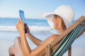 Woman relaxing in deck chair using tablet — Stock Photo