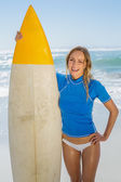 Blonde surfer holding her board — ストック写真