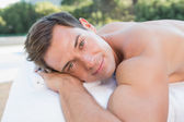 Man lying on massage table poolside — Stock Photo