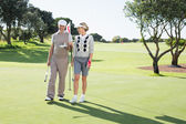 Golfing couple smiling on the putting green — Стоковое фото