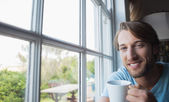 Man by window having coffee — Stock Photo