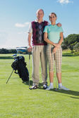 Golfing couple smiling at camera — Stock Photo