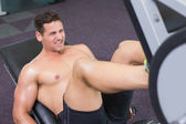Shirtless bodybuilder working with weight machine — Stock Photo