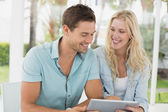 Hip couple using tablet together — Stock Photo
