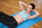 Brunette doing sit ups in fitness studio — 图库照片