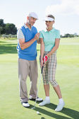 Man coaching his partner on the putting green — Stock fotografie