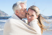 Couple wrapped up in blanket on the beach — Stockfoto