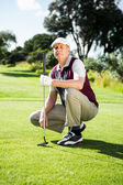 Golfer kneeling holding his golf club — Stock Photo