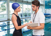 Swimmer discussing times with her coach — Stock Photo