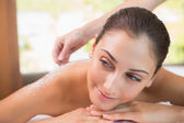 Therapist pouring salt scrub on womans back — Stock Photo