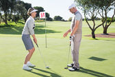 Golfer on the putting green with partner — Stock Photo