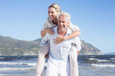 Man giving his wife a piggy back at the beach — Stock Photo