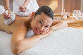 Brunette enjoying a herbal compress massage — Stock Photo